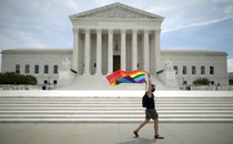 A person flies a pride rainbow flag outside the Supreme Court.