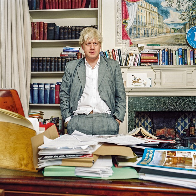 Photo: Boris Johnson standing behind messy desk by fireplace in office
