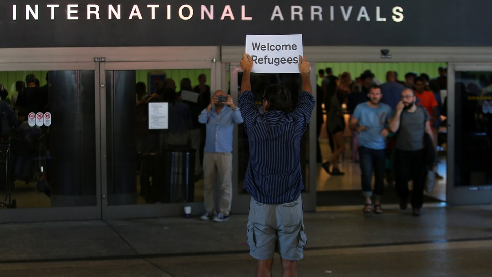 A man holds up a sign welcoming refugees at Los Angeles International Airport