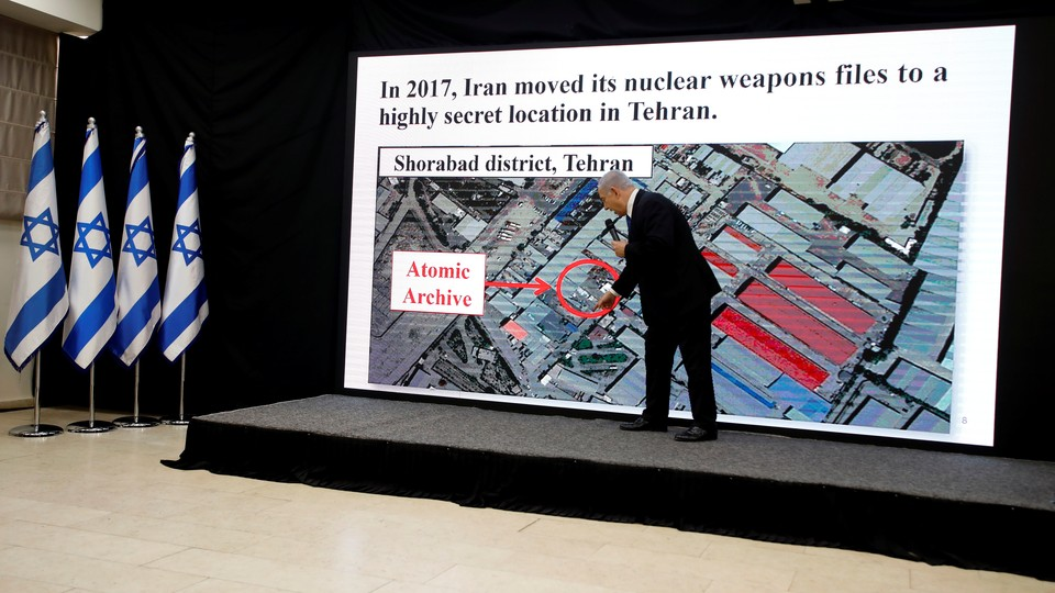 Prime Minister Benjamin Netanyahu pointing to a map on a slideshow image