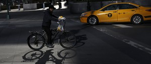 A man making deliveries rides an electric bike in New York City.