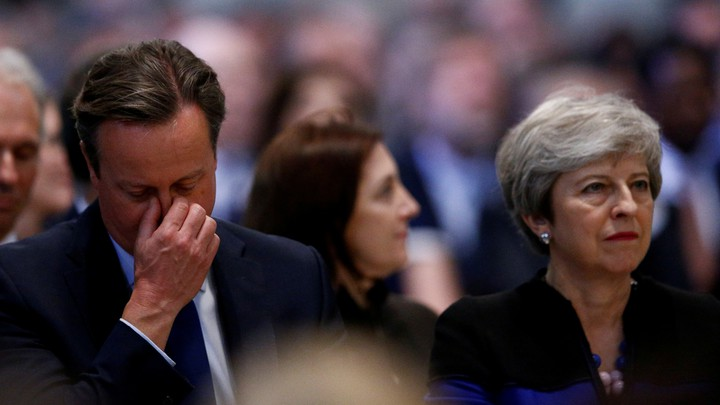 David Cameron holds his hand to his eyes as he sits alongside Theresa May at Westminster Abbey.