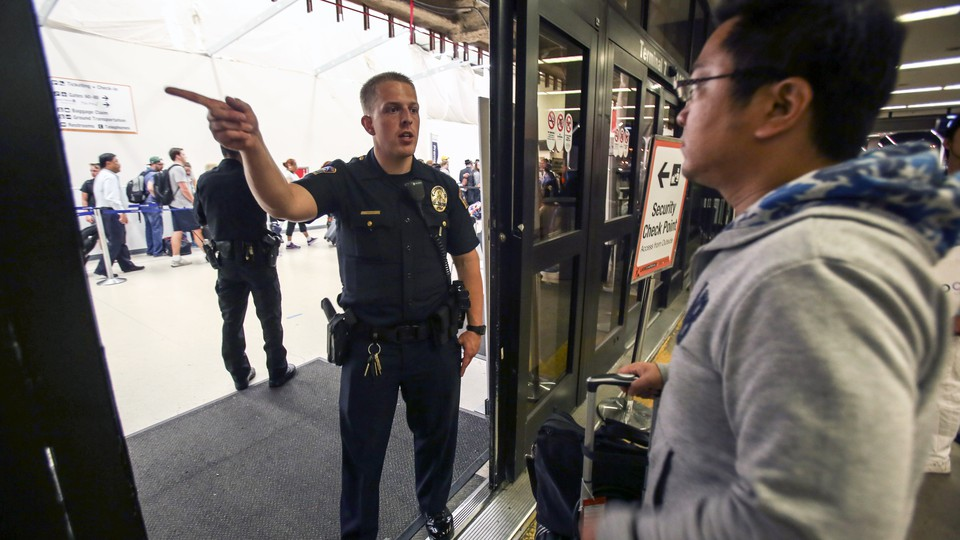 A police officer directs a passenger at Terminal 7 in Los Angeles International Airport, Sunday, Aug. 28, 2016.