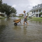 A resident pushes wheelbarrow across a flooded street in the aftermath of Hurricane Gustav in New Orleans.