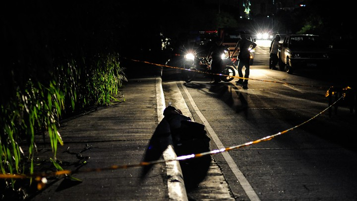 An alleged drug dealer and victim of a summary execution with his head wrapped in tape is examined by police on July 27, 2016, in Manila, Philippines.