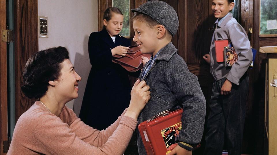 A mother sending children off to school