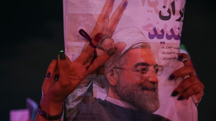 A supporter of Iranian president Hassan Rouhani holds his poster as she celebrates his victory in the presidential election, in Tehran, Iran, on May 20, 2017.