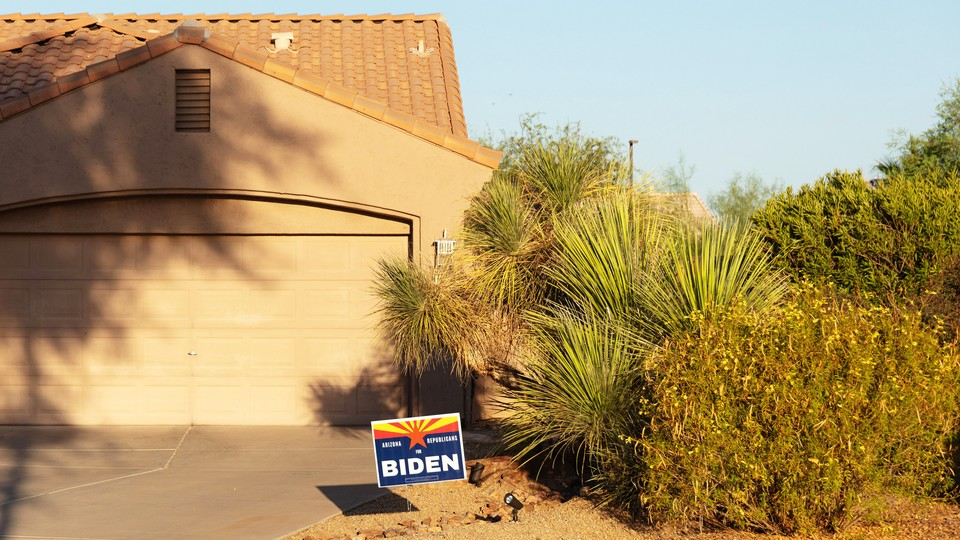 A Biden sign outside of a house with an arid, western-looking yard