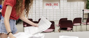 A photo of a volunteer in Omaha processing petitions to expand Medicaid for Nebraska.