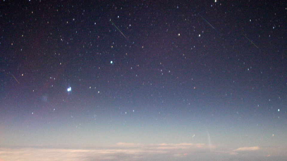 A view of meteors, originating in the constellation Auriga, streaking through the night sky