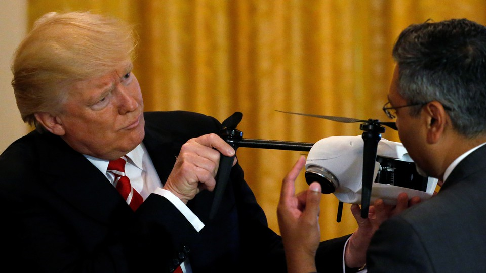 Trump holds the propellers of a small drone.
