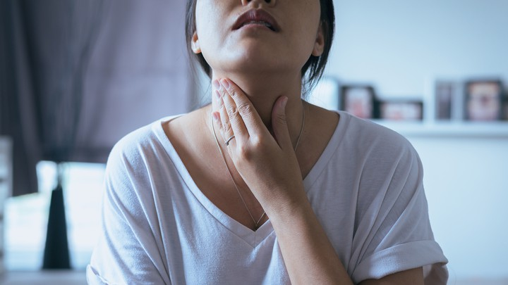 A young woman holds her neck in pain.