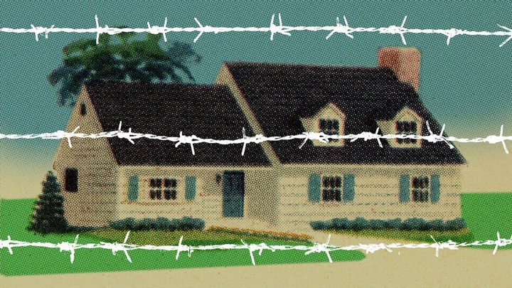 A house behind white barbed wire.