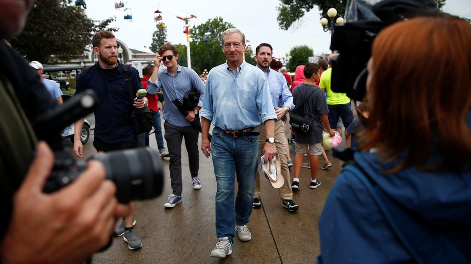 The Democratic presidential candidate Tom Steyer walks through the Iowa State Fair in Des Moines. People are surrounding him. One person, in the foreground, is pointing a camera at him.