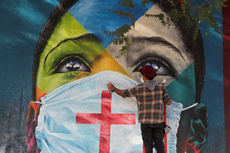 An artist stands in front of a large mural of the face of a young person wearing a mask.