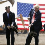 Three men wearing suits raise shovels full of dirt in front of an American flag.