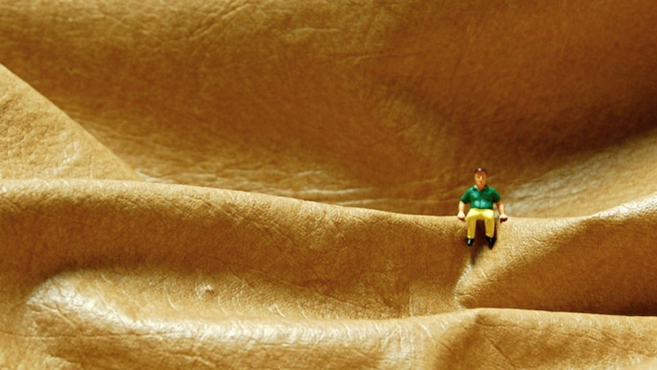A miniature figurine of a man sits perched on what looks like folds of leather.