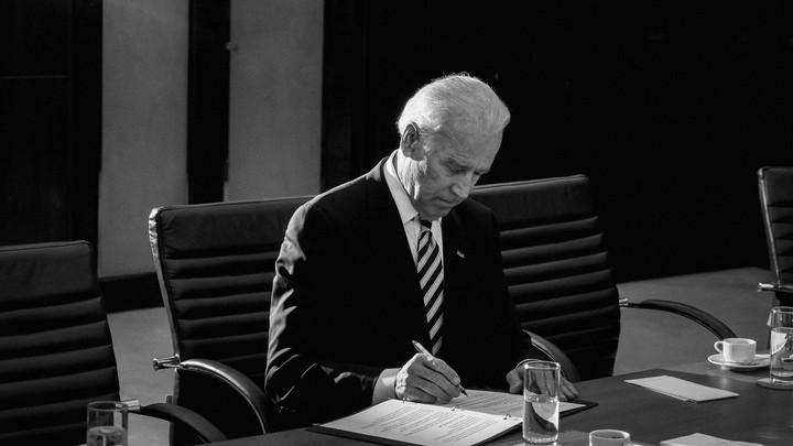 Biden signs a document.