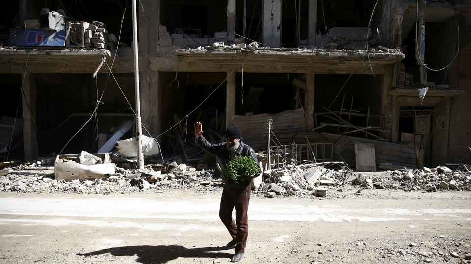 A bearded man waves outside the shell of a bombed-out building.