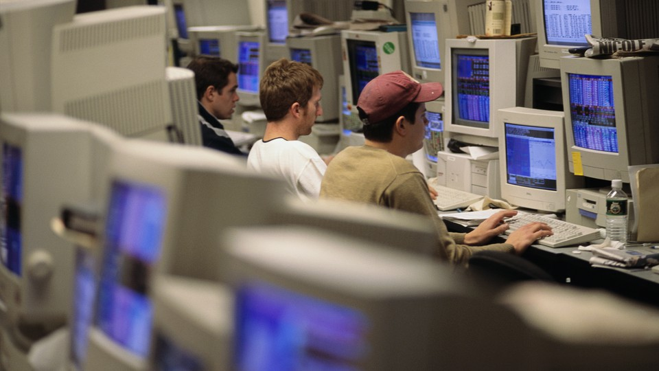 Three young men in a room full of computers