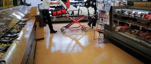 Medics take a woman out of a grocery store where she was found unresponsive after overdosing on opioids.