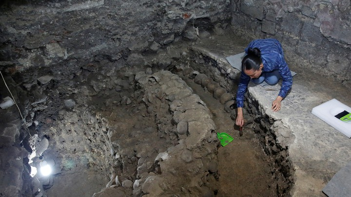 Lorena Vazquez, an archaeologist from the National Institute of Anthropology and History (INAH), works at a site where more than 650 skulls caked in lime and thousands of fragments were found in the cylindrical edifice near Templo Mayor.