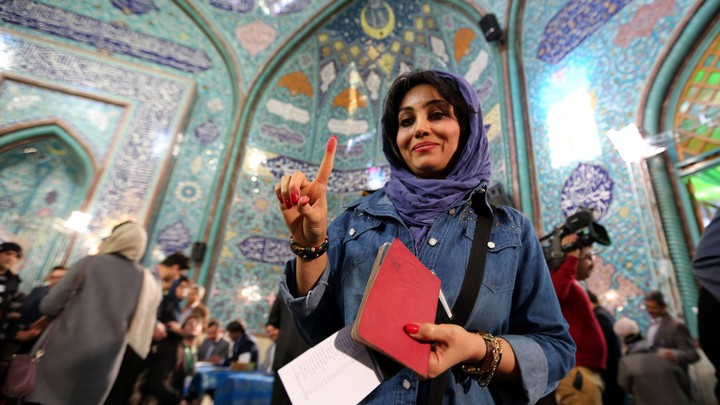 An Iranian woman shows her inked finger after casting her ballot at a polling station in Tehran on February 26, 2016.