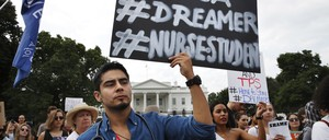 An undocumented immigrant who is a recipient of DACA and a nursing student stands in front of the White House protesting the Trump administration's phasing out of the program.