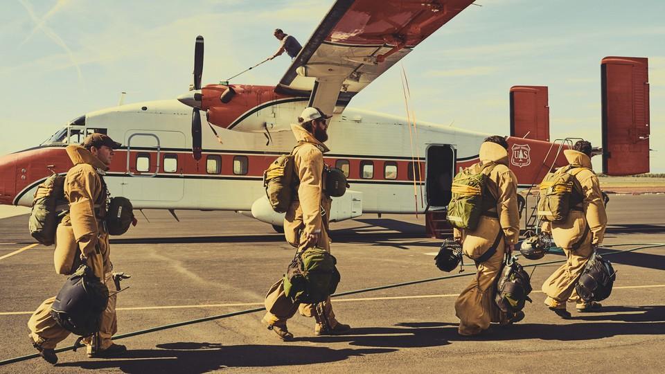 Smoke jumpers in gear boarding a plane