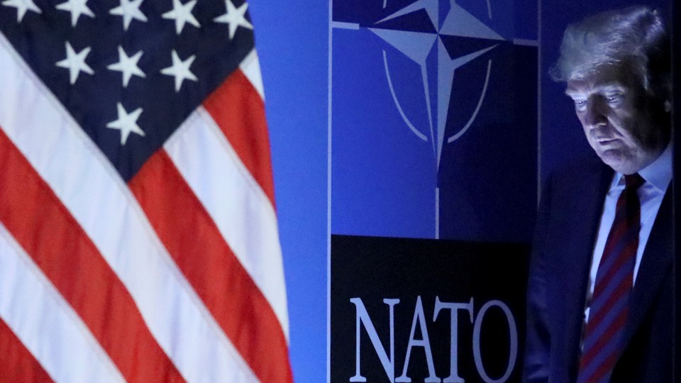 Donald Trump walks onto the stage to deliver a press conference at the NATO summit in Brussels