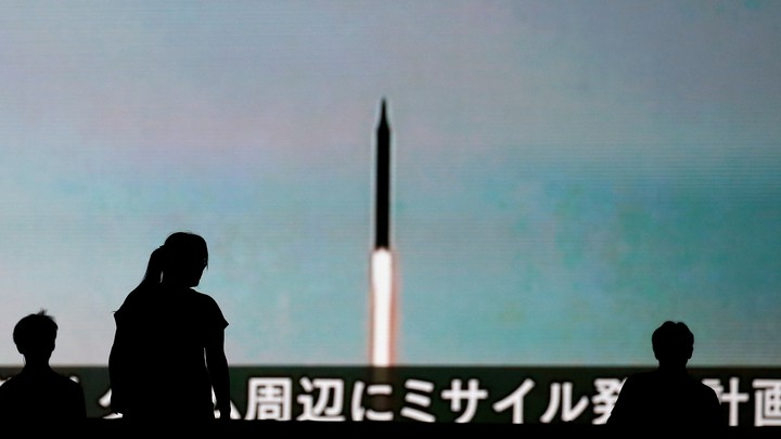 People walk in front of a monitor showing news of North Korea's fresh threat in Tokyo