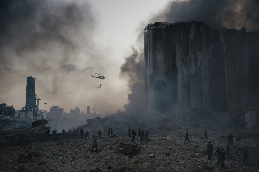 A helicopter flies over the wreckage left by a massive explosion in Beirut.