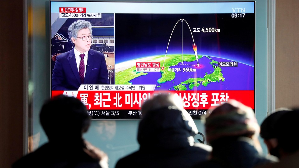 People watch a television broadcast of a news report on North Korea firing what appeared to be an intercontinental ballistic missile.