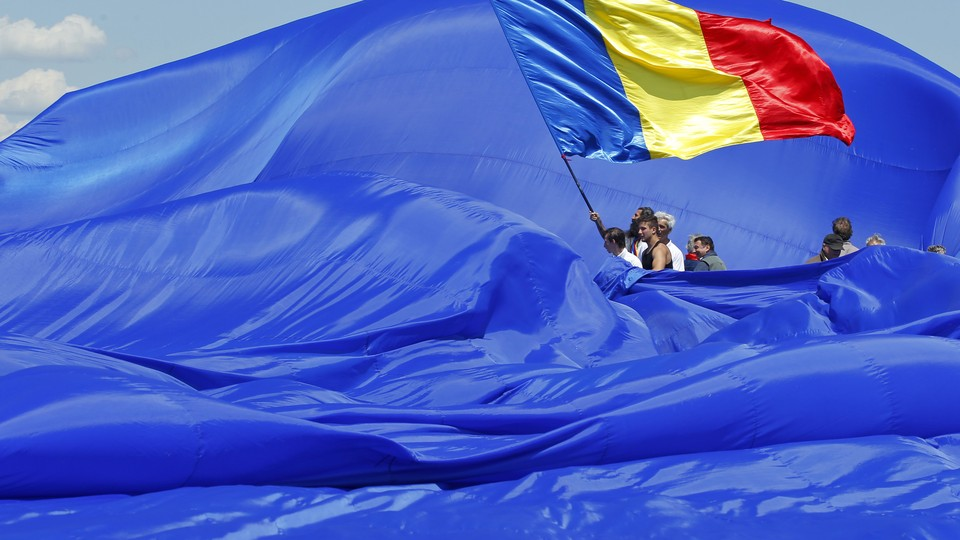 Workers arrange Romania's national flag during a Guinness World Record attempt for the world's biggest national flag.