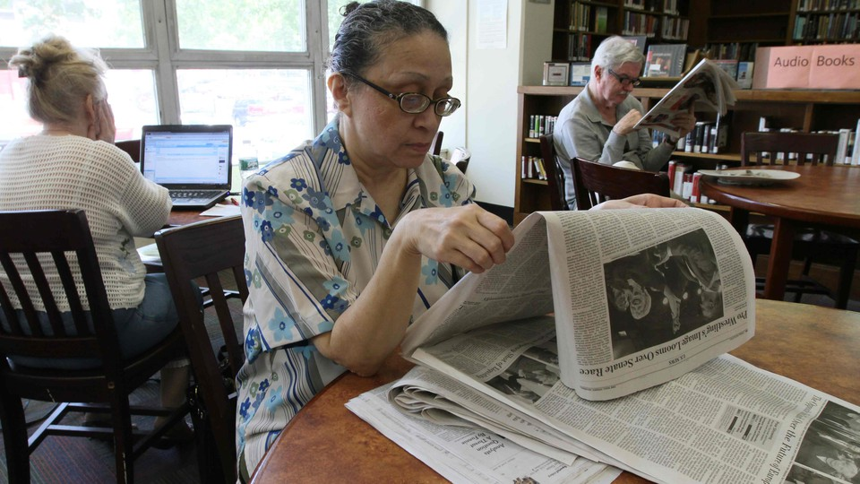 A woman reads a newspaper in a library.