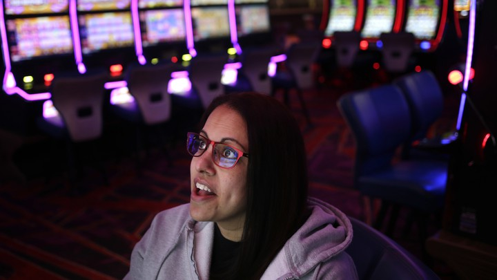 A woman wearing glasses looks up at a screen