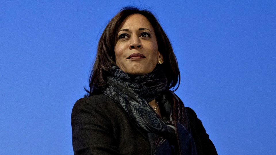 A photo of Kamala Harris wearing a black jacket and patterned scarf, against a blue backdrop