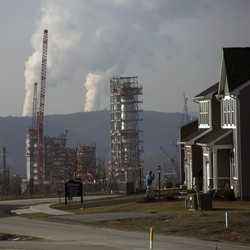 A smoking fracking project sits behind a suburban subdivision and beneath a gray, smoggy sky.