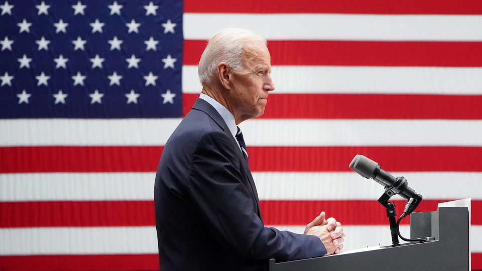 Standing in front of a podium, Joe Biden pauses while delivering remarks into a microphone. A large American flag is visible behind him.