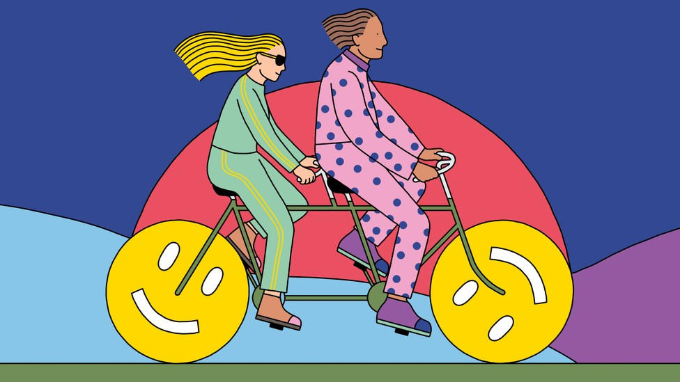 Two people ride a tandem bicycle, the wheels of which are smiley faces.