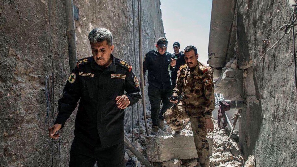 Iraqi officers pictured on the ruins of the Grand al-Nuri Mosque in Mosul, Iraq on June 29, 2017.