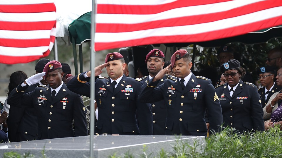 U.S. soldiers salute the casket of U.S. Army Sergeant La David Johnson with U.S. flags flying in the background.