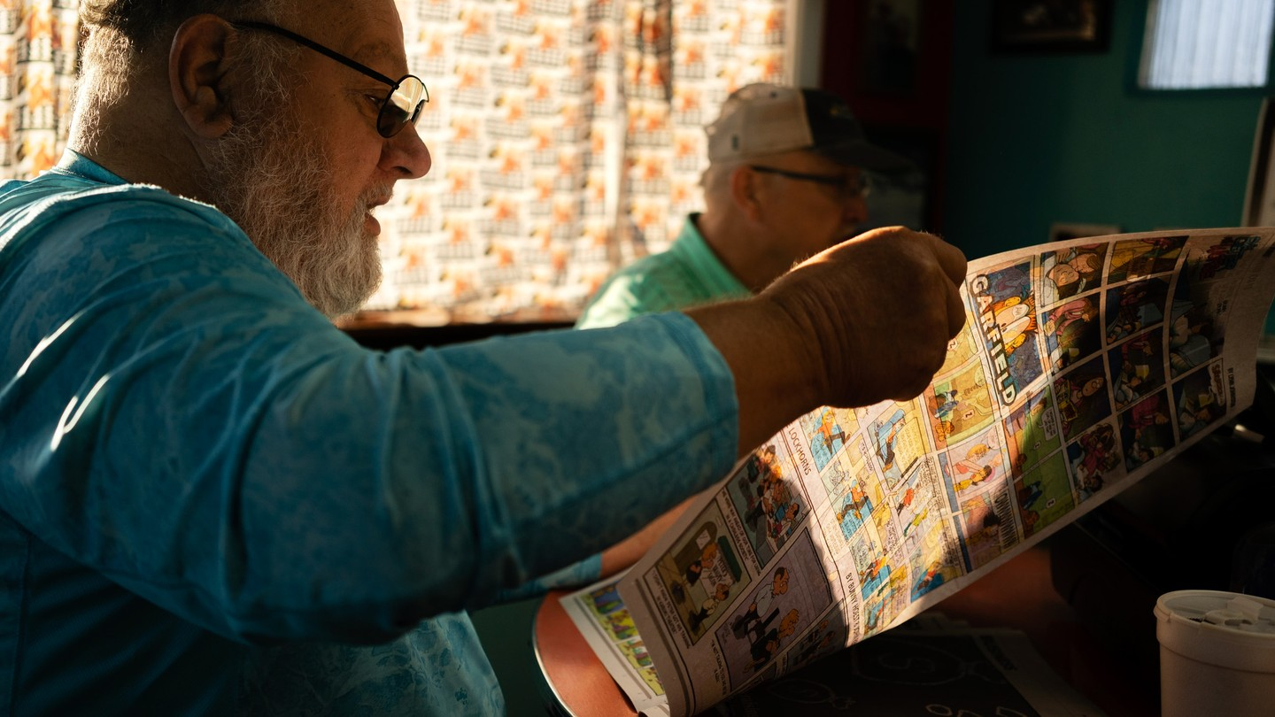 A man is reading The Hawk Eye newspaper in a diner.