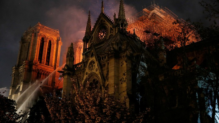Sparks fill the air as Paris fire-brigade members spray water to extinguish flames as Notre-Dame Cathedral burns.