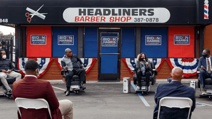 Kamala Harris speaks as part of a panel outside a barbershop.