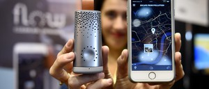 A woman displays a small sensing device and a smartphone with a pollution app.