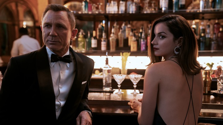 Daniel Craig and Ana de Armas dressed in black cocktail attire at a bar for a scene in 'No Time to Die'