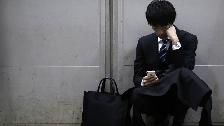 A man leaning against a wall looks down passively at his iPhone