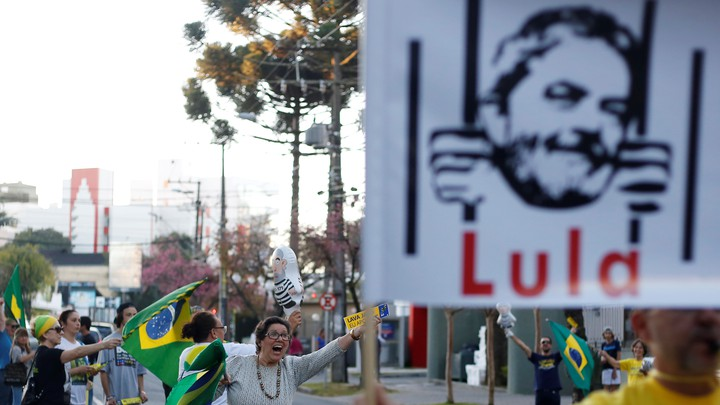 People celebrate and hold up a sign of former president Lula da Silva behind bars.
