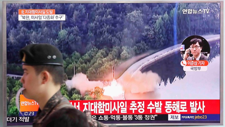 A South Korean soldier walks past a TV broadcast of a news report on North Korea firing what appeared to be several land-to-ship missiles off its east coast, at a railway station in Seoul, South Korea, on June 8, 2017.